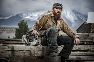 Man with long beard sits on wood wearing Patagonia workwear, with mountains in the background.