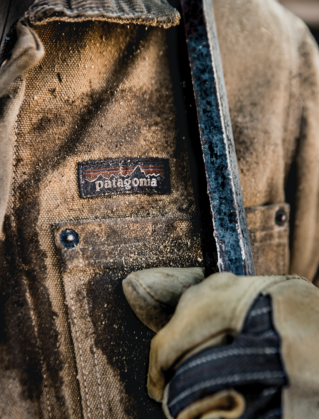 A gloved hand holds a metal bar up to the chest of a tan Patagonia workwear jacket.