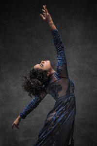 Ballet dancer striking a pose in sheer and navy dress.