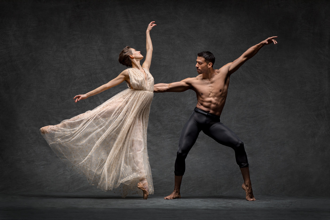 Two ballet dancers strike poses while dancing against dark backdrop.
