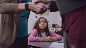Girl looking up at a handshake between 2 adults, looking sad.