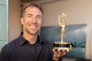 Tyler smiling and holding the Emmy Award he won for directing a Turning Point documentary.