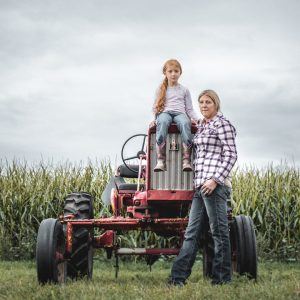 A mother and daughter sit on a tractor, looking at the camera with a grey sky in the background.