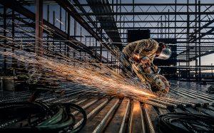 A steel worker sends sparks flying as he works in a steel yard.