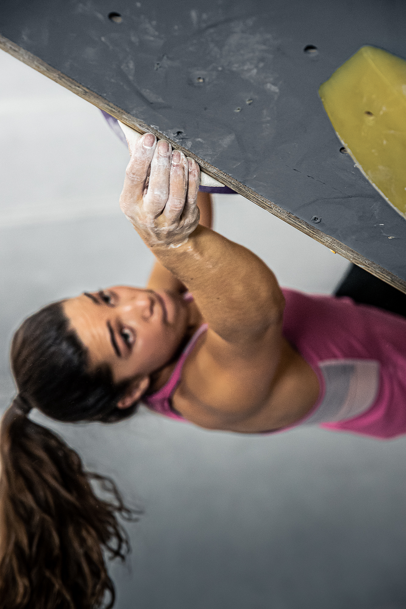 Brooke Raboutou reaches up and grabs a hold on a bouldering wall at Mesa Rim Climbing Academy.