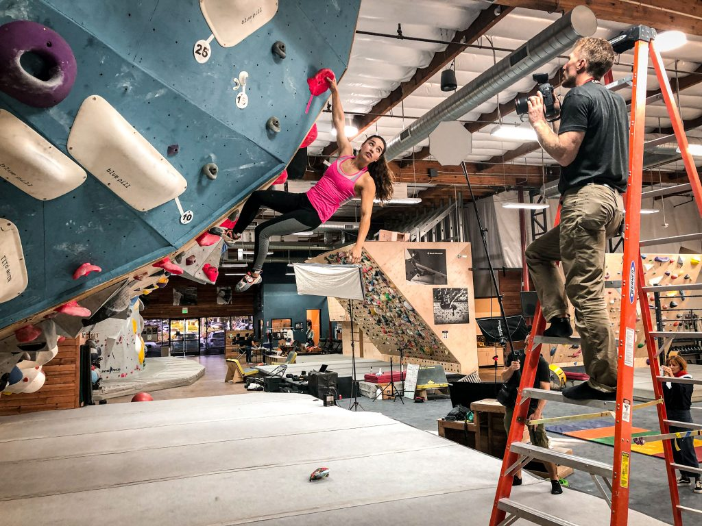 Olympic climber Brooke Raboutou hangs off a hold on a bouldering wall while photographer Tyler Stableford gives her direction.
