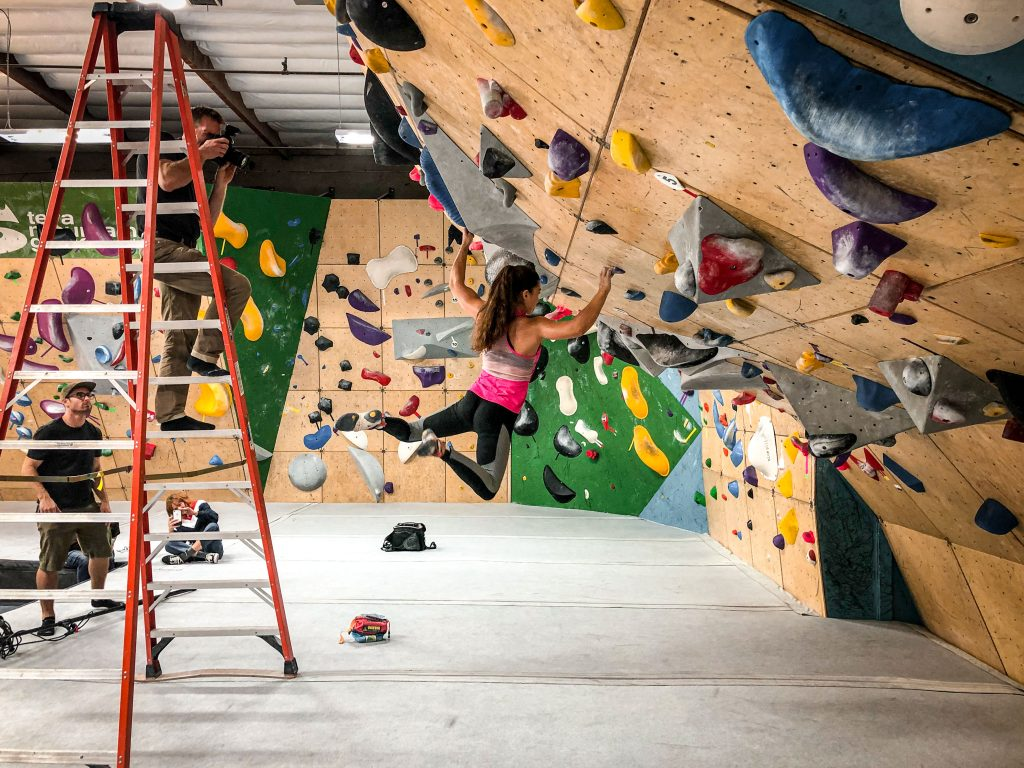 Olympic climber Brooke Raboutou hangs off a hold on a bouldering wall while photographer Tyler Stableford stands on a ladder.