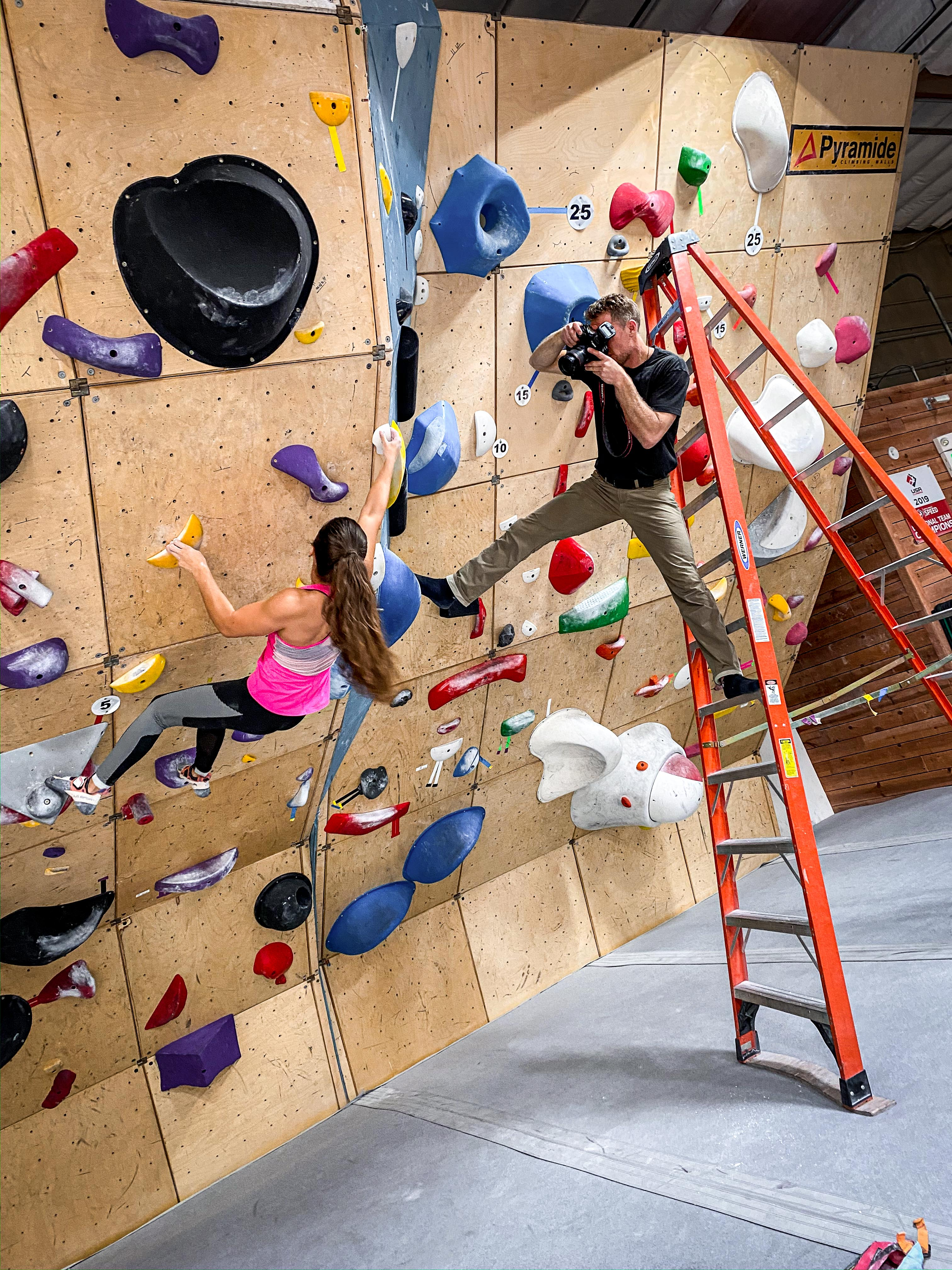 Tyler balances himself on a ladder and the climbing wall as he photographs Brooke.