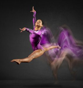 Olympic gymnast Jessica Lopez leaps with motion blur behind her.