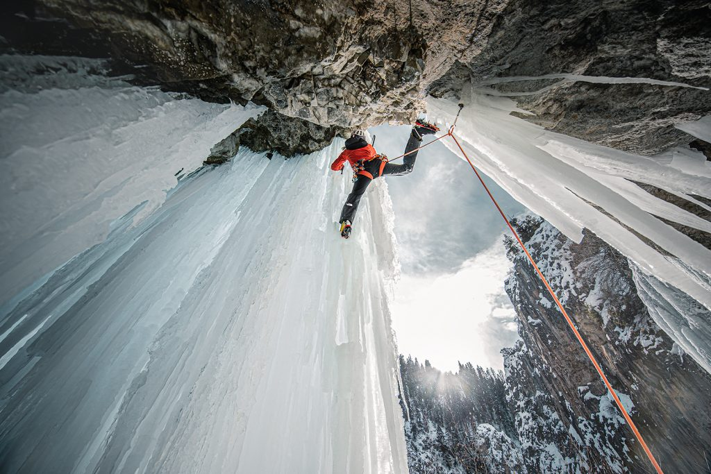 Climber Anna Pfaff stretches to reach her next step while ice climbing.