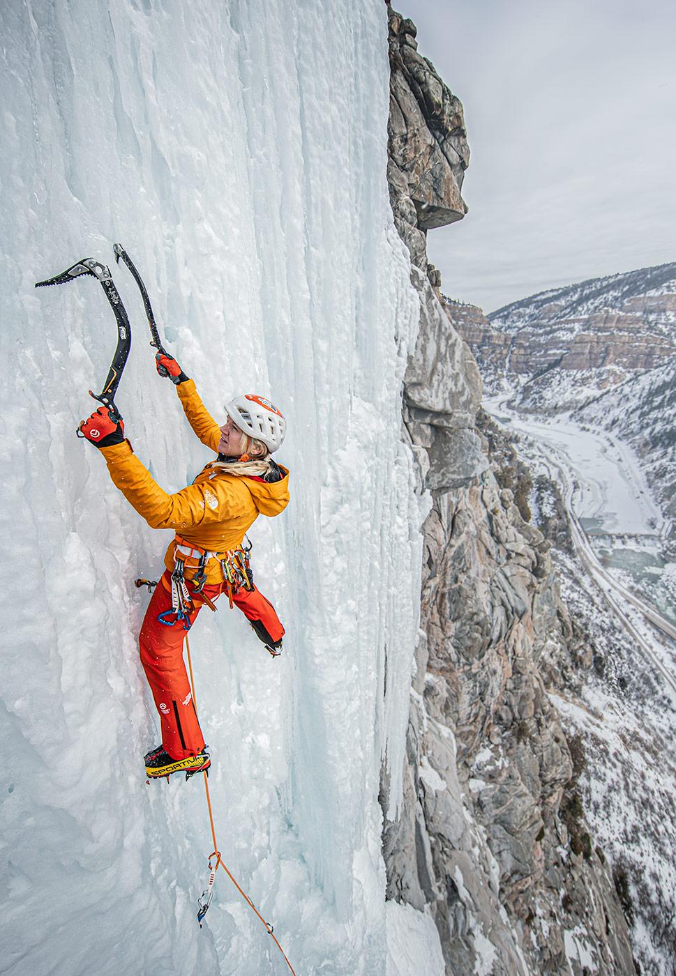 A woman ice climbs high above a Colorado landscape.