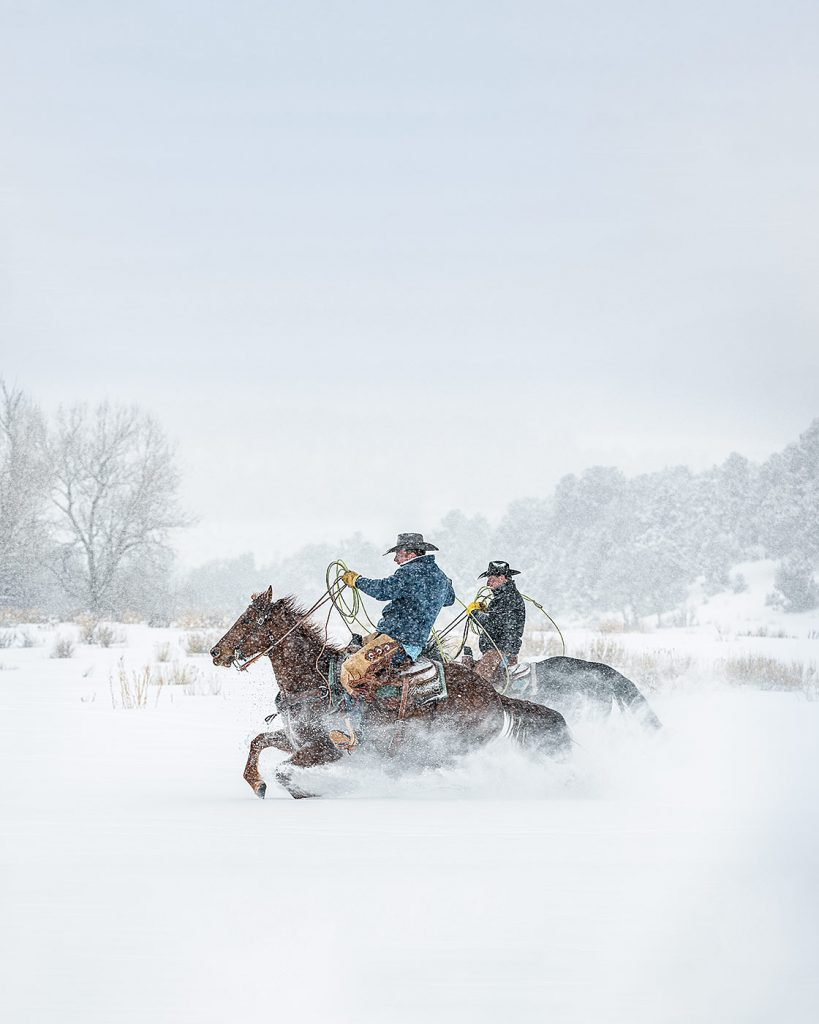 Cowboys on horses gallop through a snowstorm