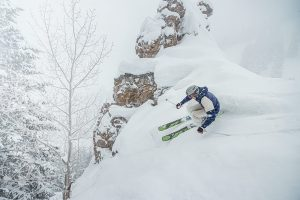 A skier slashes powder by a cliff on Aspen Mountain